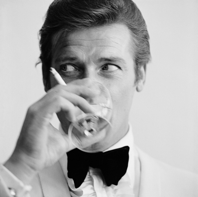 17th July 1968: English film star Roger Moore, well known for his roles as James Bond and the Saint, downs a martini. (Photo by Peter Ruck/BIPs/Getty Images)